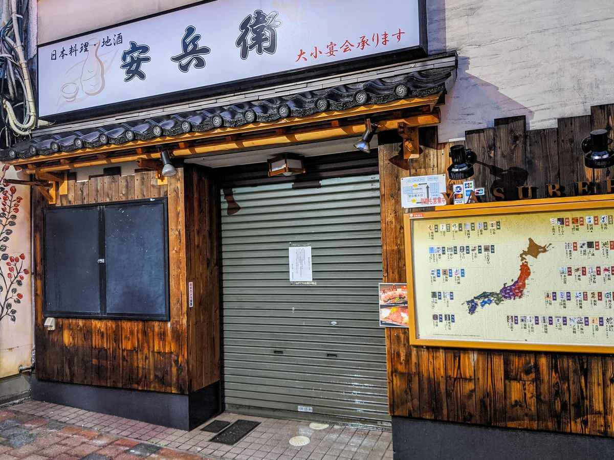 A restaurant on Omoide Yokocho with a closed sign taped to the door.