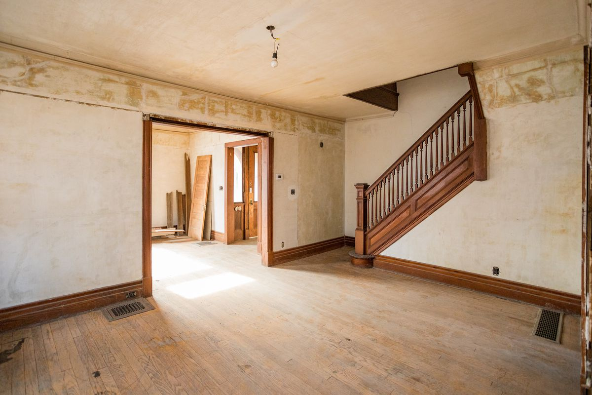 An empty room with aged hardwood floors and off color walls.