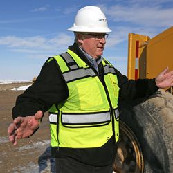 Bruce McDonough, project manager with Layton Okland,  discusses construction of the new prison as crews build a temporary road to access the new site, seen behind him, in Salt Lake City on Wednesday, Dec. 28, 2016.