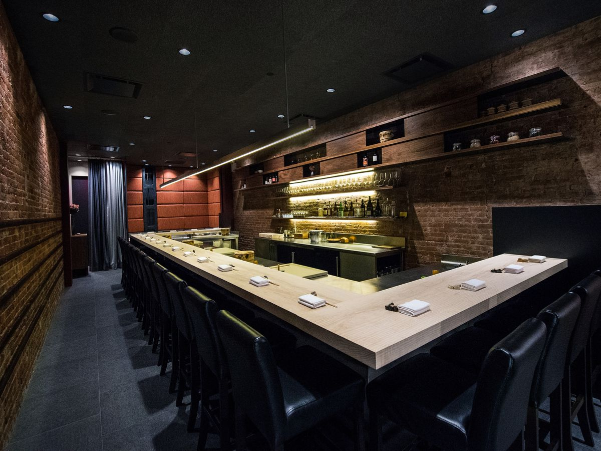 A dimly lit sushi restaurant with tables arranged around an L-shaped counter