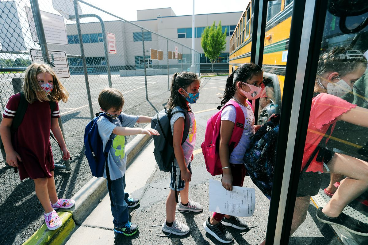 Students at Woodrow Wilson Elementary School in South Salt Lake wear masks as they get on a bus