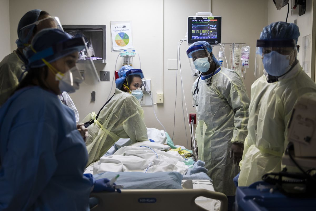 Nurse practitioner Capri Rees, left, looks at the monitor for a heart rhythm while respiratory therapist Khafran Alshahin performs chest compressions on an 80-year-old man who ultimately died from COVID-19 at Roseland Community Hospital in April of 2020.