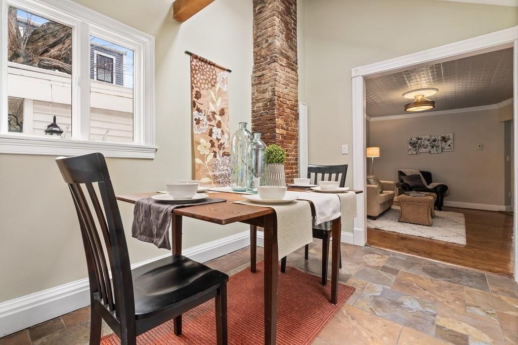 Small dining room just beyond a wide opening and with a table and two chairs.