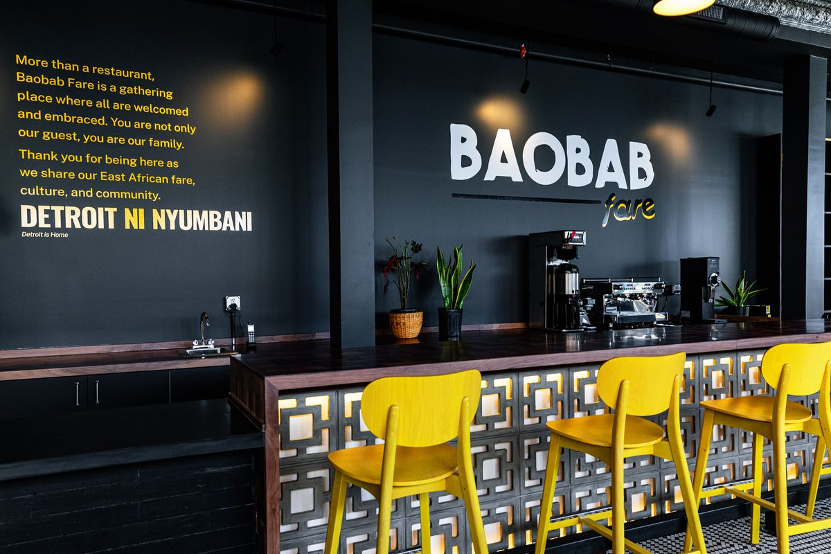 Three bright yellow bar stools in front of a sleek black and gray bar at Baobab Fare in Detroit. A coffee machine and espresso machine sit along the back bar.