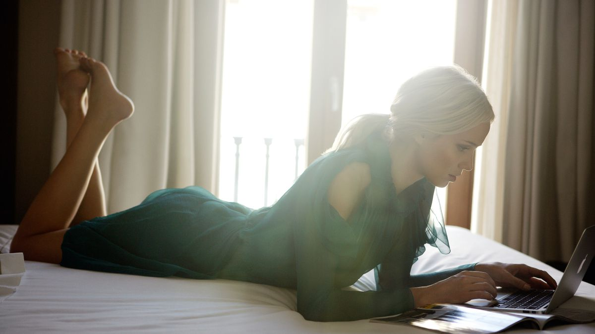 A woman using a tablet while lying on a bed