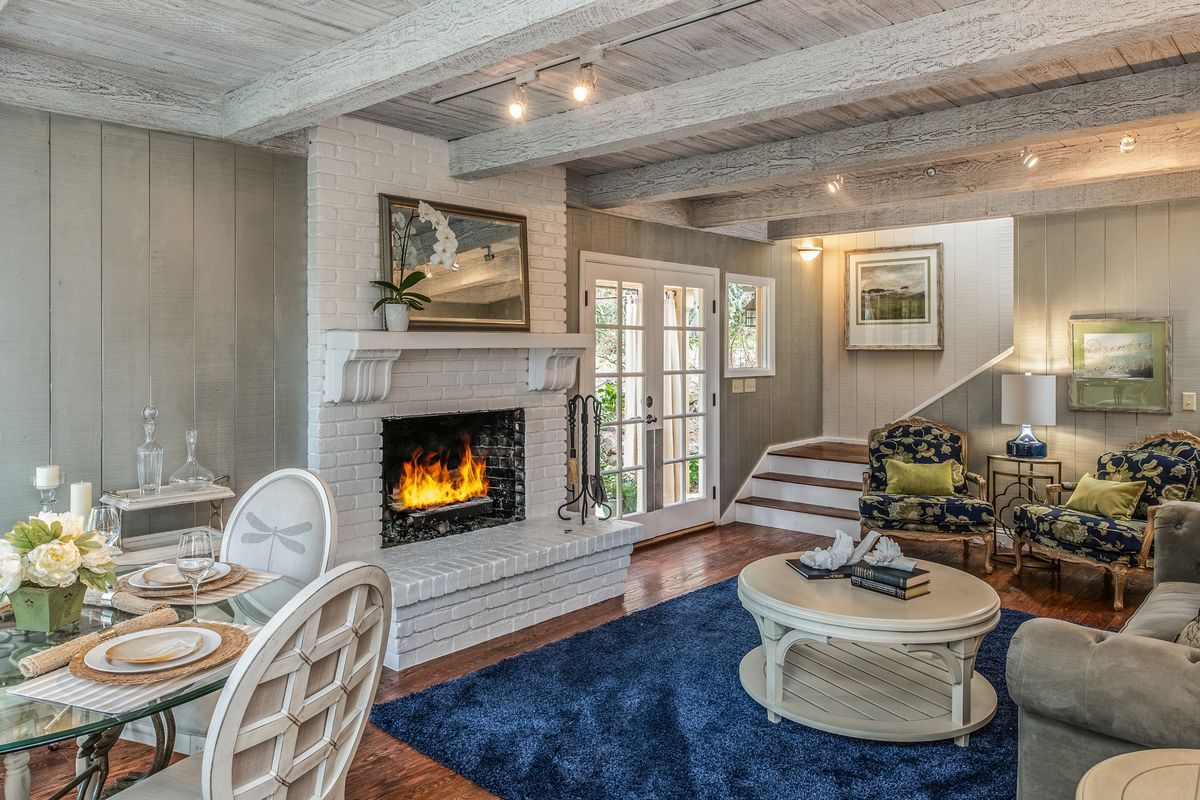 A white fireplace and exposed beams in a living room. There is a blue rug with a round rattan white coffee table.