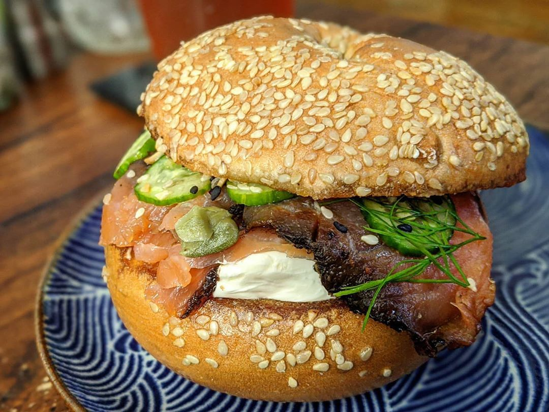 Closeup of lox, cream cheese, and pickles on a sesame bagel