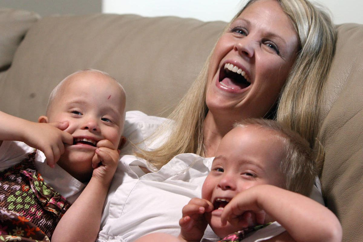 Natasha, left and her sister Abigail make faces at their dad Josh as they sit with their mother Kimberly Tillotson in the family room of their home Friday, June 22, 2012 in Murray. Abigail and Natasha are identical twins with Down Syndrome.