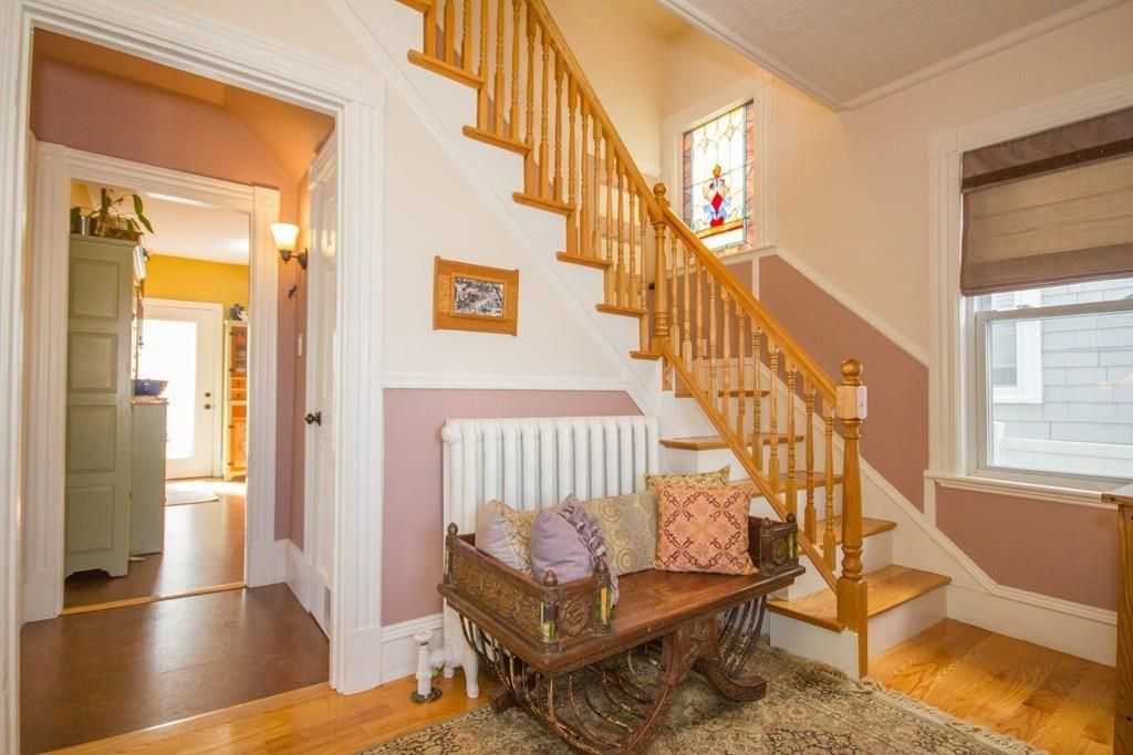 An entry foyer with a stairwell and a bench with pillows in front of a radiator.