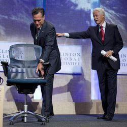 Former President Bill Clinton reaches out for Republican presidential candidate, former Massachusetts Gov. Mitt Romney as he grabs his notes after speaking at the Clinton Global Initiative convention in New York, Tuesday, Sept. 25, 2012.