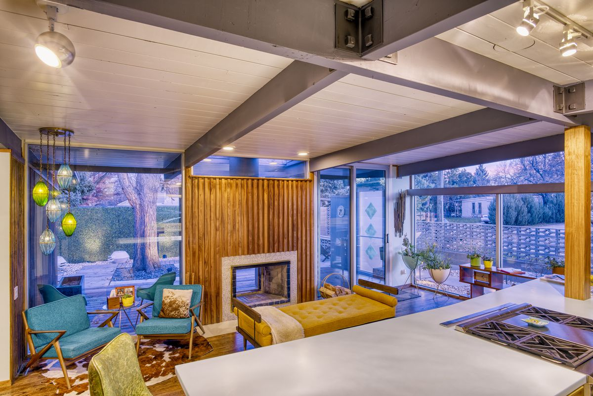 The interior of a midcentury modern home. There is a couch, chairs, planters, light fixtures, a fireplace, and floor to ceiling windows. There is a wood paneled wall around the fireplace.
