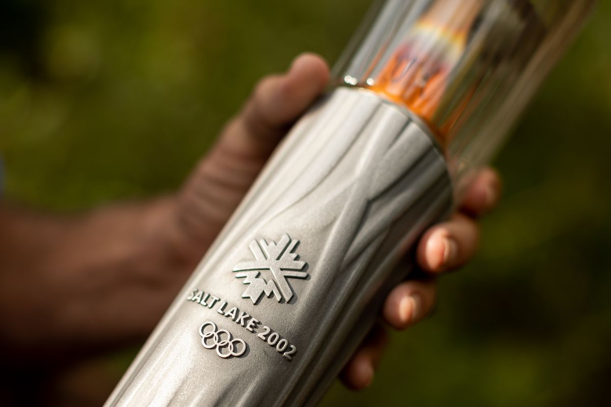 Fraser Bullock, who served as chief operating officer for the Salt Lake Organizing Committee for the 2002 Winter Olympics, holds one of that year's Olympic torches while he poses for a photograph at his home in Alpine on Tuesday, Aug. 31, 2021.