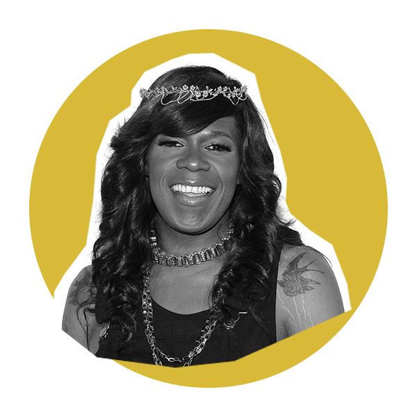 A black and white photo of Big Freedia with long curled hair, wearing a black tank top, chain necklace, and a tiara.