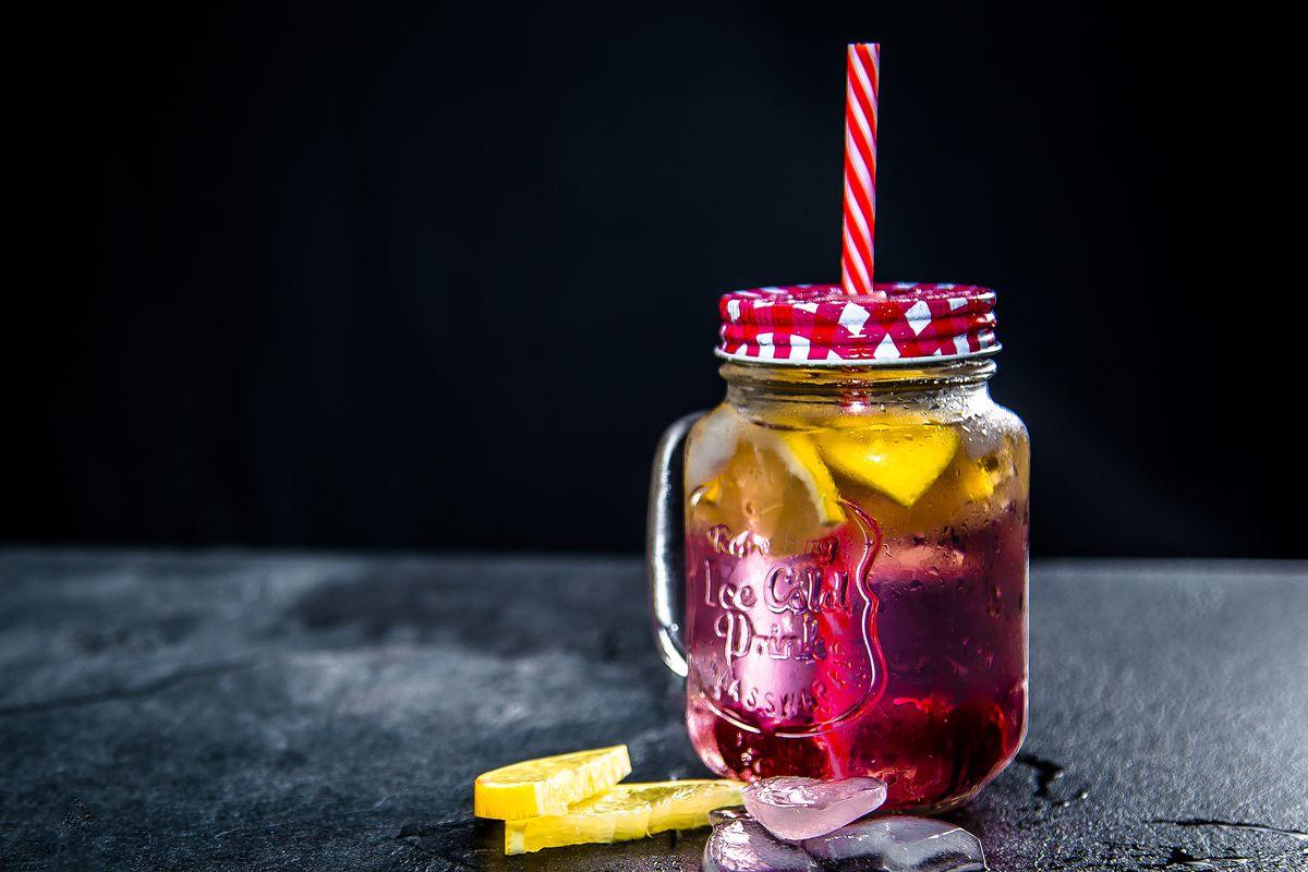 mason jar with lid and straw and reddish liquid inside