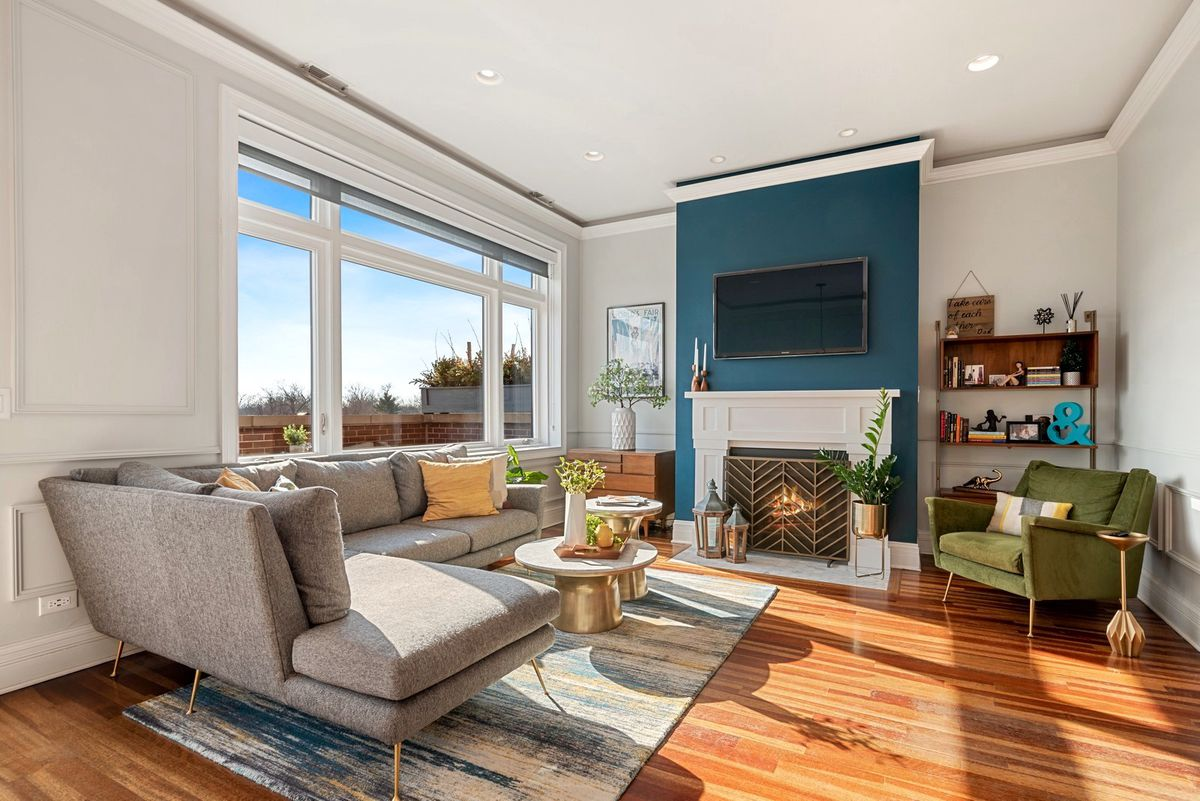 A room with a large picture window, hardwood floors, and a fireplace set against a blue accent wall.