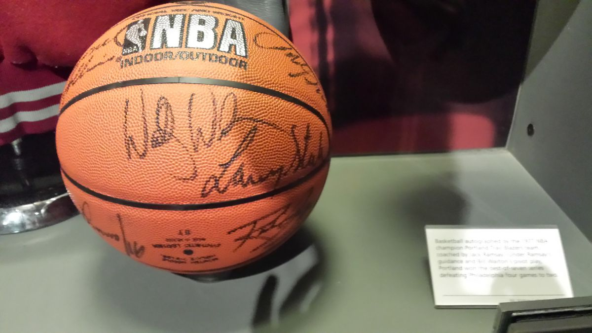 Basketball covered in autographs in a display case.