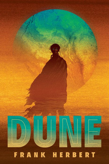 the cover of Dune: Deluxe Edition; a figure profiled in a cloak rises up against a turquoise moon that stains an orange background; the figure has bright turquoise eyes that match the moon, although there are no other recognizable facial features