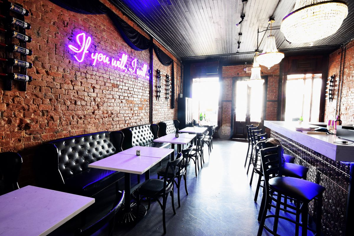 """The interior of a restaurant with a brick wall lined with black leather booths on the left. A neon pink, cursive word sign on the wall reads """"if you will, I will."""" A long, white-topped bar lined with tall stools  is on the right."""