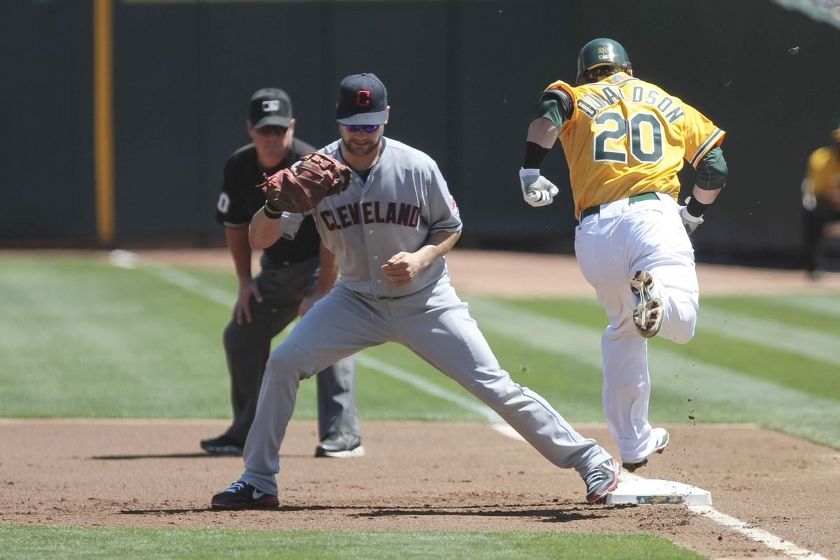 August 19, 2012; Oakland, CA, USA; Cleveland Indians first baseman Casey Kotchman (left) forces out Oakland Athletics third baseman Josh Donaldson (20) during the first inning at O.co Coliseum. Mandatory Credit: Kelley L Cox-US PRESSWIRE