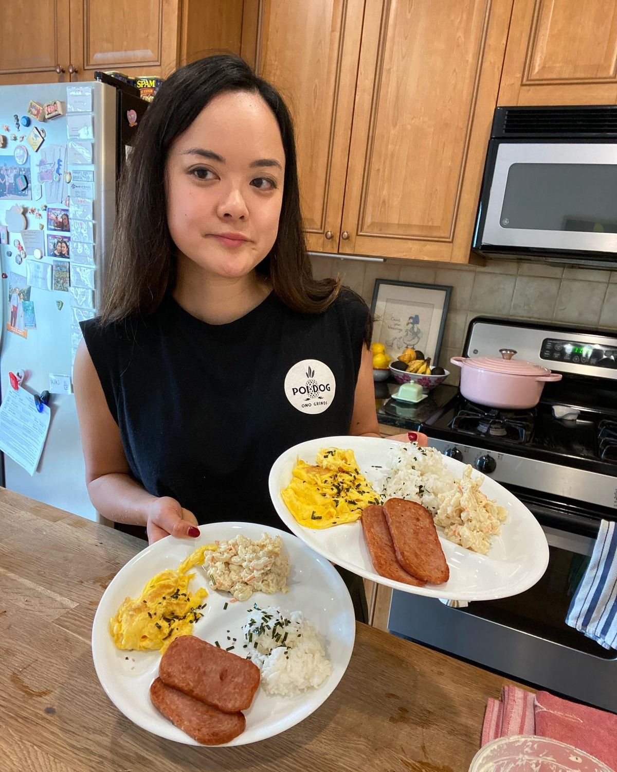 woman standing in home kitchen holding two plates of food