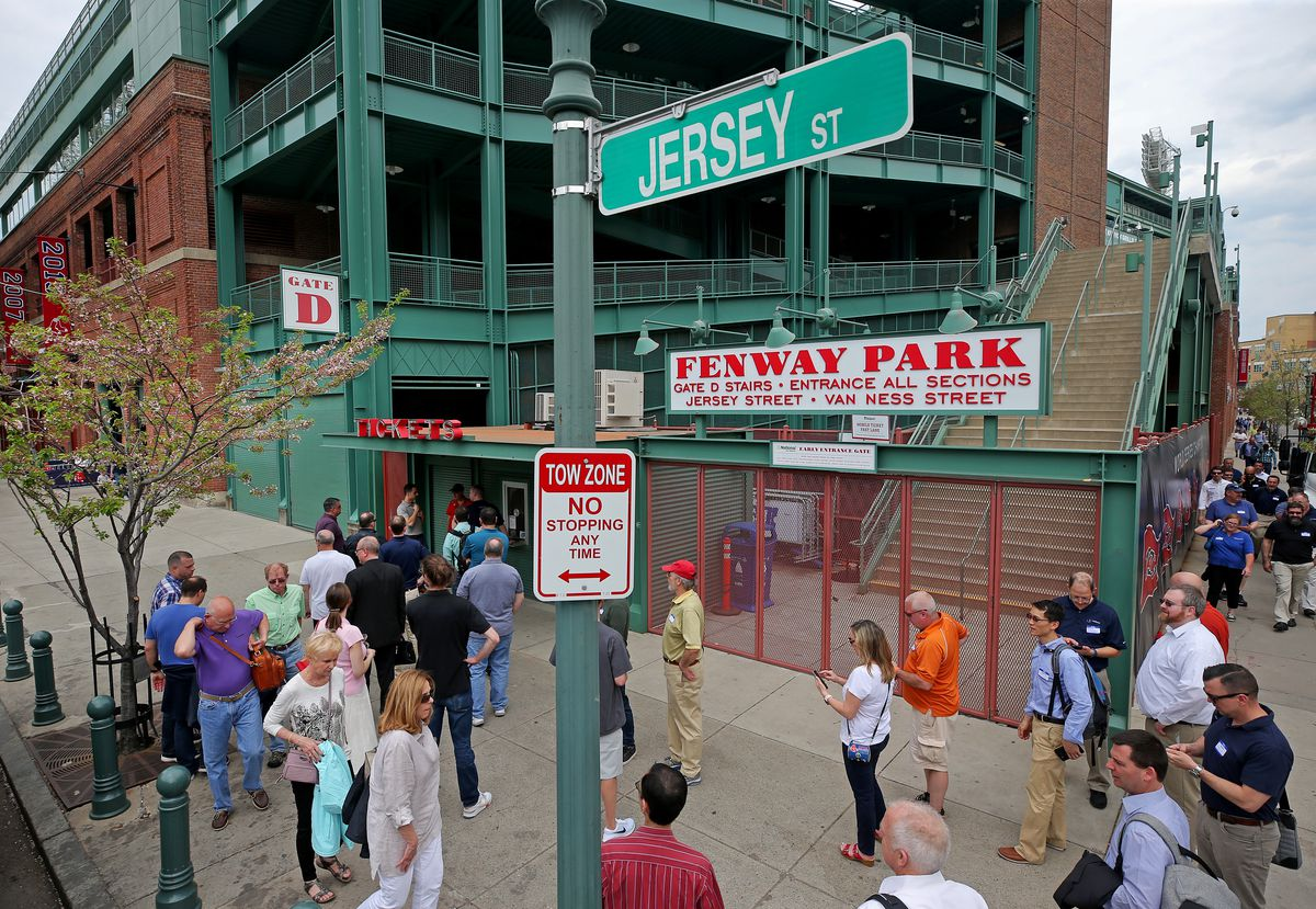 People milling about outside of a ballpark.