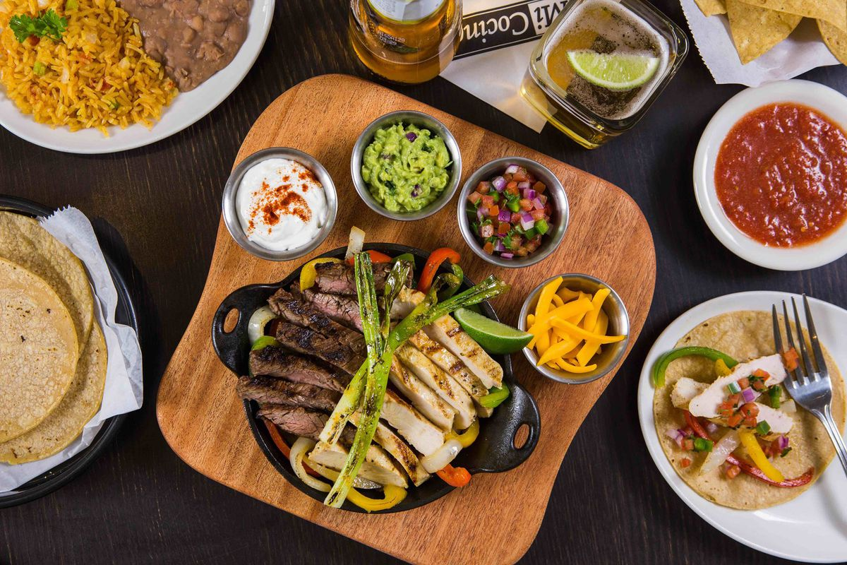 a plate of chicken and beef fajitas with toppings on the side