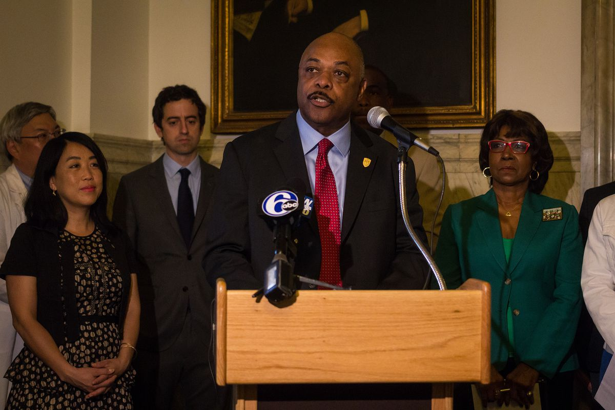 Jerry Jordan standing at a podium speaking into microphones.