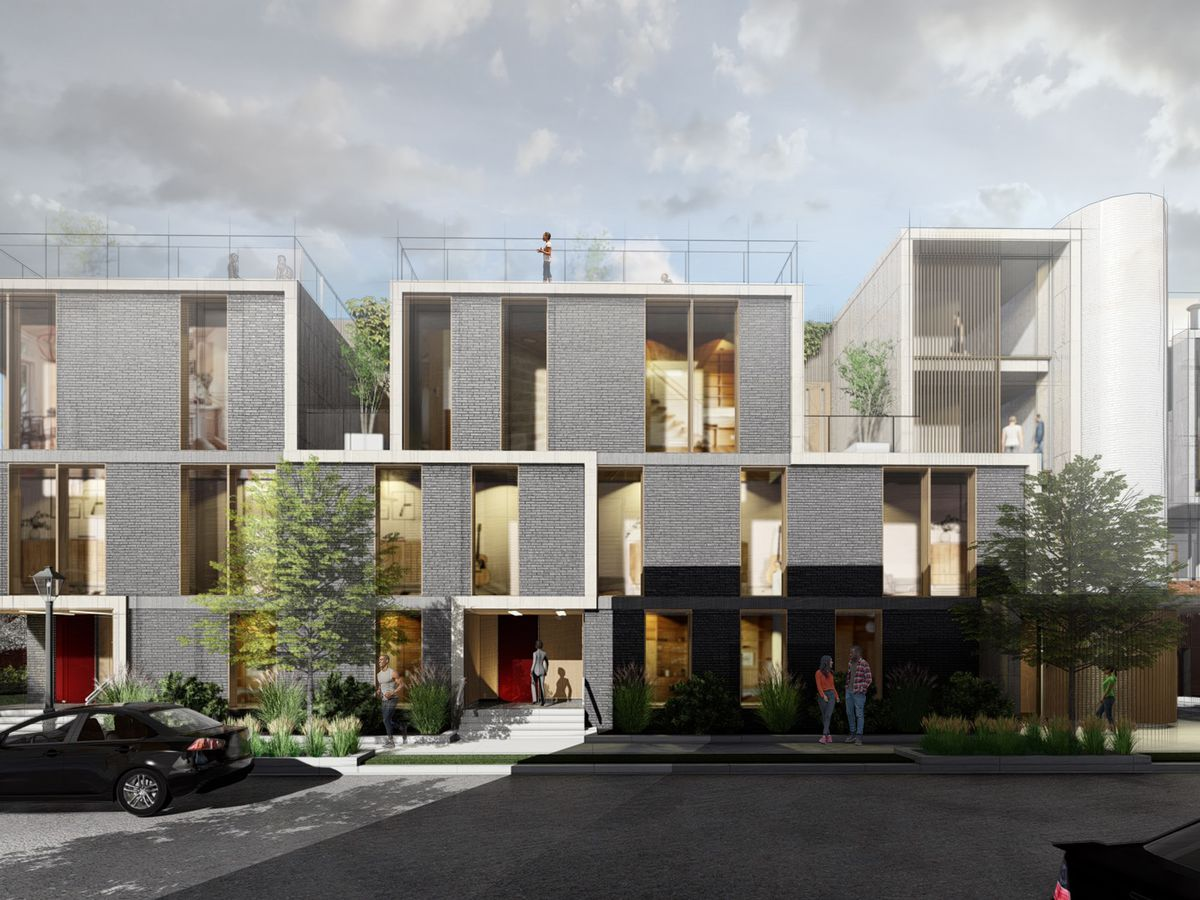 The exterior of a group of townhomes in Detroit. The building facade consists of multiple geometric shapes with grey brick.