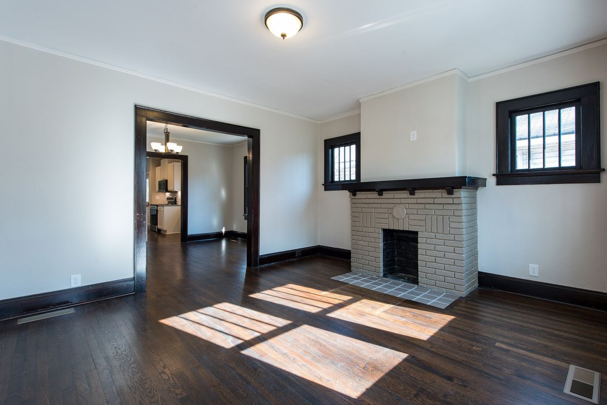 Empty living room with gray brick fireplace and windows on each side of the fireplace.