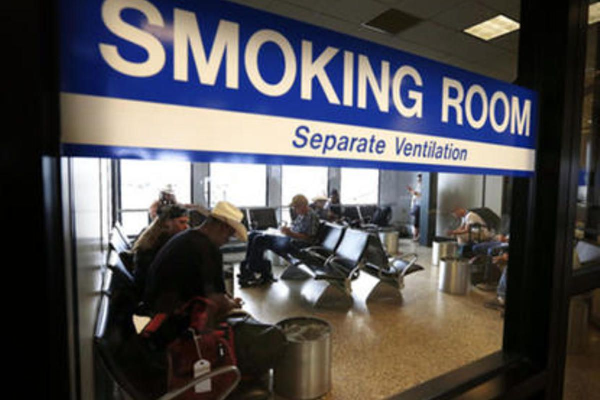 FILE: Travelers use a smoking room at Salt Lake City International Airport, Monday, Aug. 3, 2015.