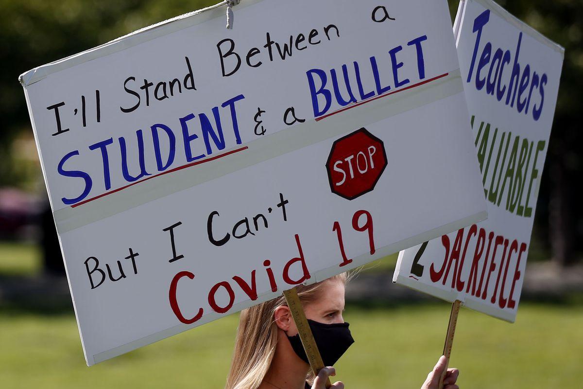 A teacher protests, urging masks in schools.