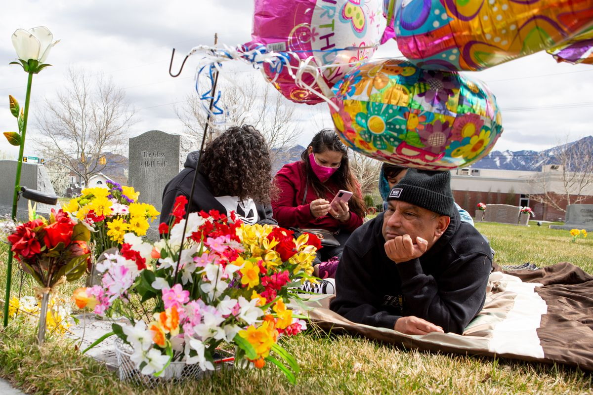"""Eddie Chavez listens to a song his mother enjoyed while his daughter Karol Chavez, center, and her children Jessedie Chavez, left, and Isaac Chavez, 9, accompany him on a visit to his mother's cemetery plot on her birthday at Murray City Cemetery on Sunday, April 12, 2020. Eddie Chavez usually visits his mother's cemetery plot with about 25 members of his family on her birthday, April 11, but he went the following day with only his daughter and grandchildren, who live with him. His sister visited the site Saturday. They have been keeping their distance due to concerns of being considered at high risk of contracting COVID-19. """"My sister and I are very close. Wherever I go she goes with me. We get together often as family,"""" Eddie Chavez said. His sister dropped off homemade masks at the family's door earlier this week."""