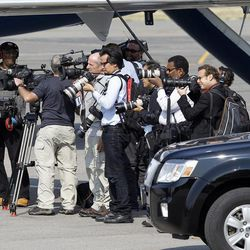 Media watches as Mitt Romney arrives in Salt Lake City, Tuesday, Sept. 18, 2012.