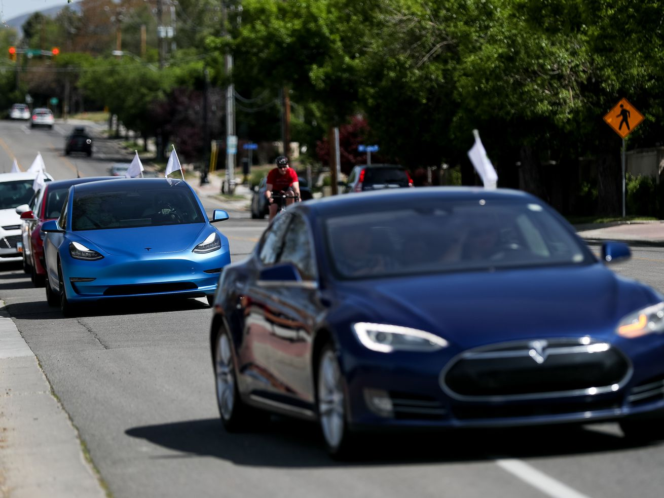 Teslas and other electric vehicles take off from the Holladay City Office for an electric vehicle parade on Saturday, May 16, 2020.