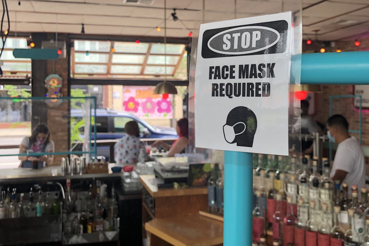 """A bar with a """"face mask required"""" sign on its counter."""
