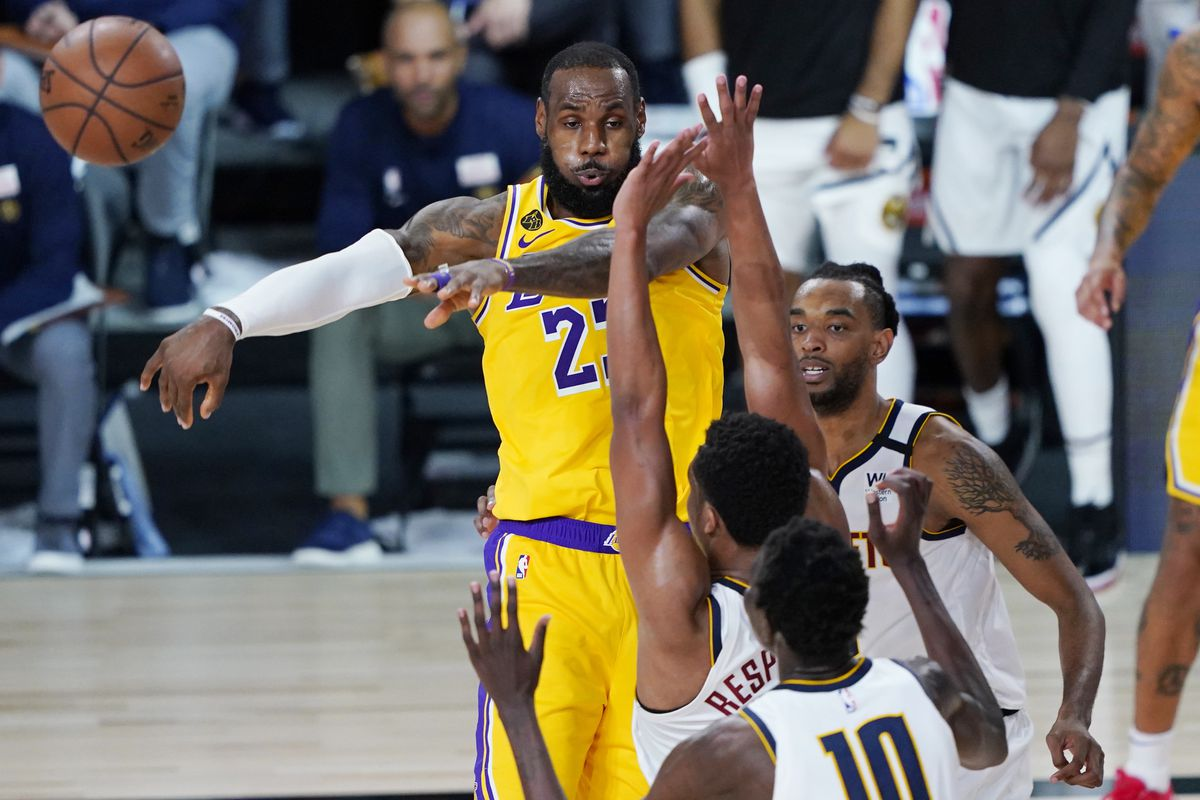 Los Angeles Lakers' LeBron James passes the ball during the second half of an NBA basketball game against the Denver Nuggets, Monday, Aug. 10, 2020, in Lake Buena Vista, Fla. at AdventHealth Arena.