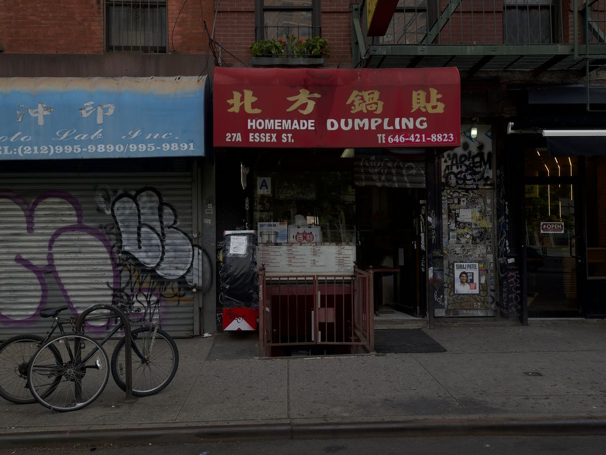 """A storefront on a city street has a red awning with the words """"Homemade Dumpling"""""""