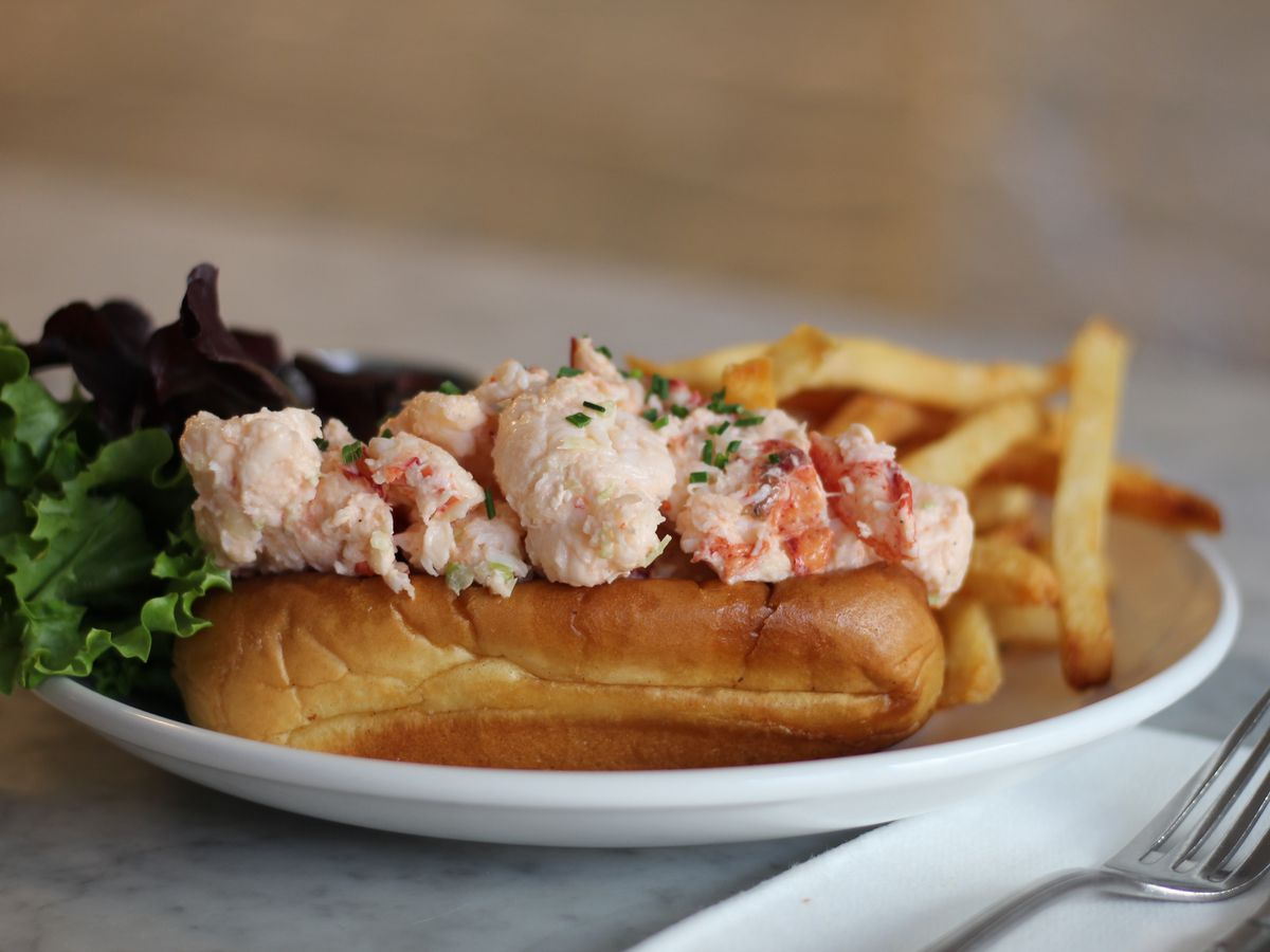 A close-up photo of a lobster roll with green lettuce and fries on the side sitting on a white plate with a napkin and fork in the foreground