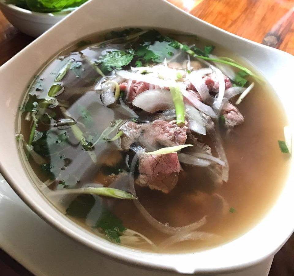 Pho with brown broth, rare beef, white and green onions, and cilantro is served in a white bowl