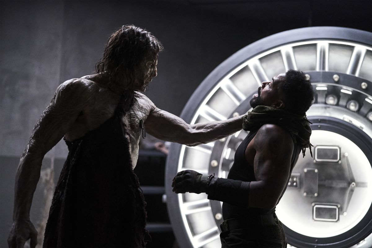An alpha zombie holds Rich Cetrone by the throat in front of a lit-up bank-vault door in Army of the Dead