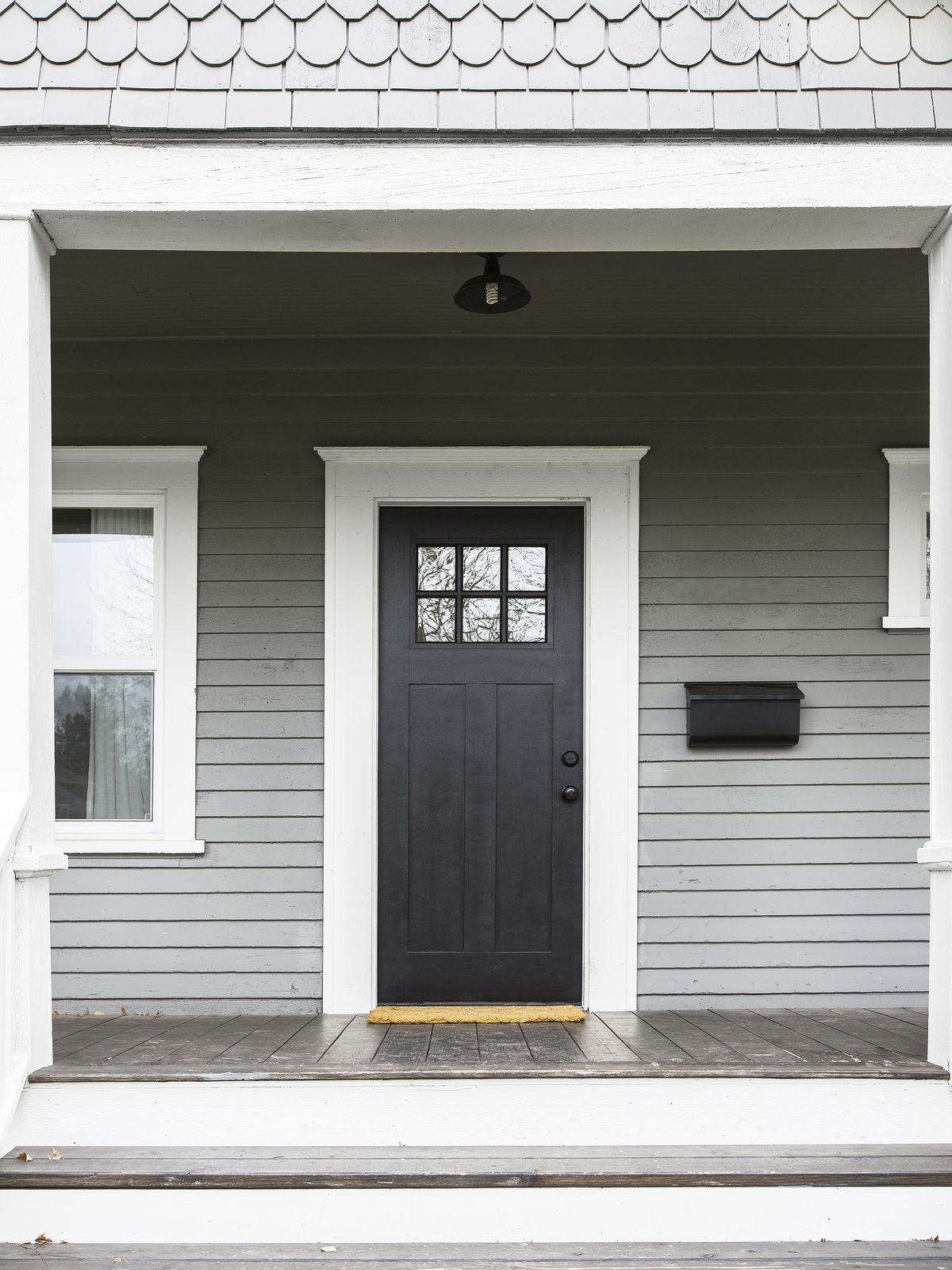 The exterior entryway of a house. The door is black and the doorway is white. The house is grey panels. The mailbox is black.