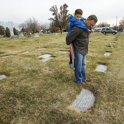 Randy Thompson carries his nephew Davin Thompson while visiting family graves at the Murray Cemetery in Murray Nov 19, 2014. Several Thompson family members have died from cancer.
