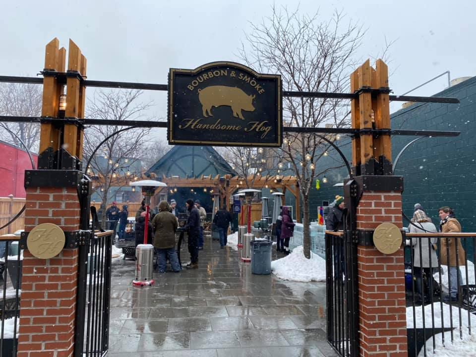 A spaced out group of people on a snowy day at the Handsome Hog with fire pits and ice bars along the edges of the patio.