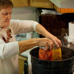 Bobbie Davis, of Provo, Utah,  cans tomatoes and peaches delivered by her neighbor Loren Boddy Thursday, Sept. 13, 2012. Determined to not let any food go to waste, Boddy picks unused fruit and vegetables throughout his neighborhood and delivers it to those who will eat or can it.
