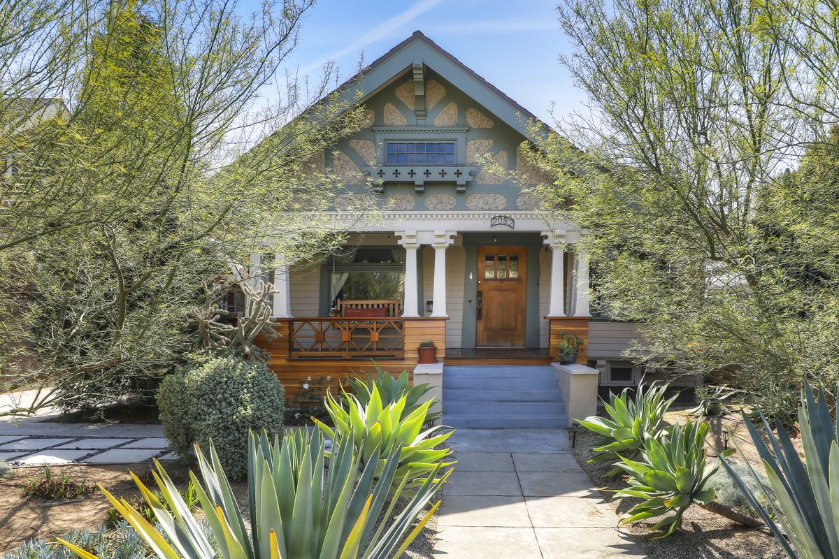 A single-story Craftsman with landscaping obscuring it.