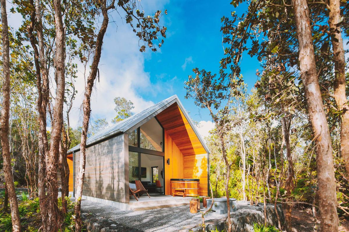 Exterior shot of A-frame cabin surrounded by trees.