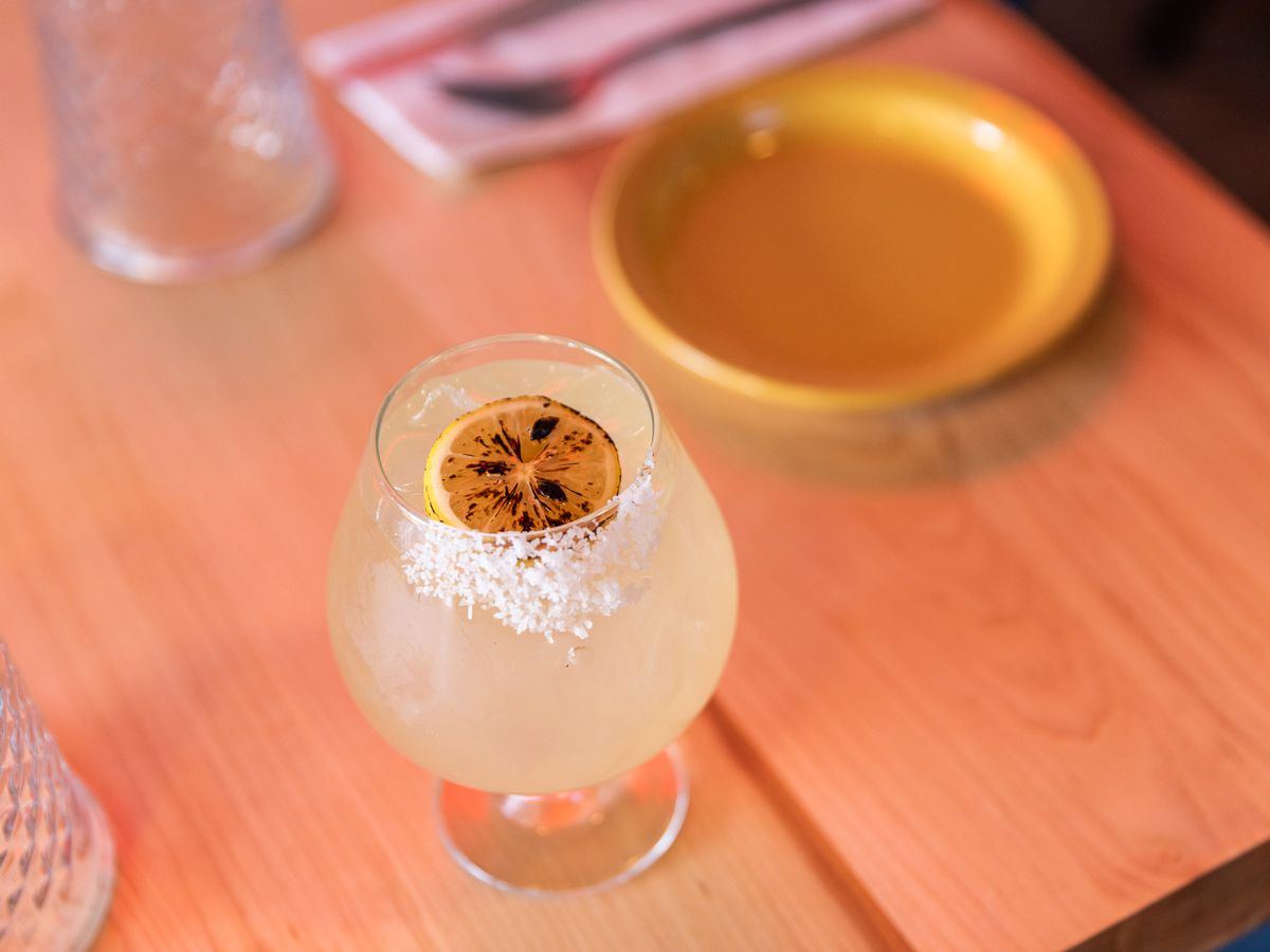 A yellow margarita in a tulip glass with a slice of charred lemon on top next to the salted rim.