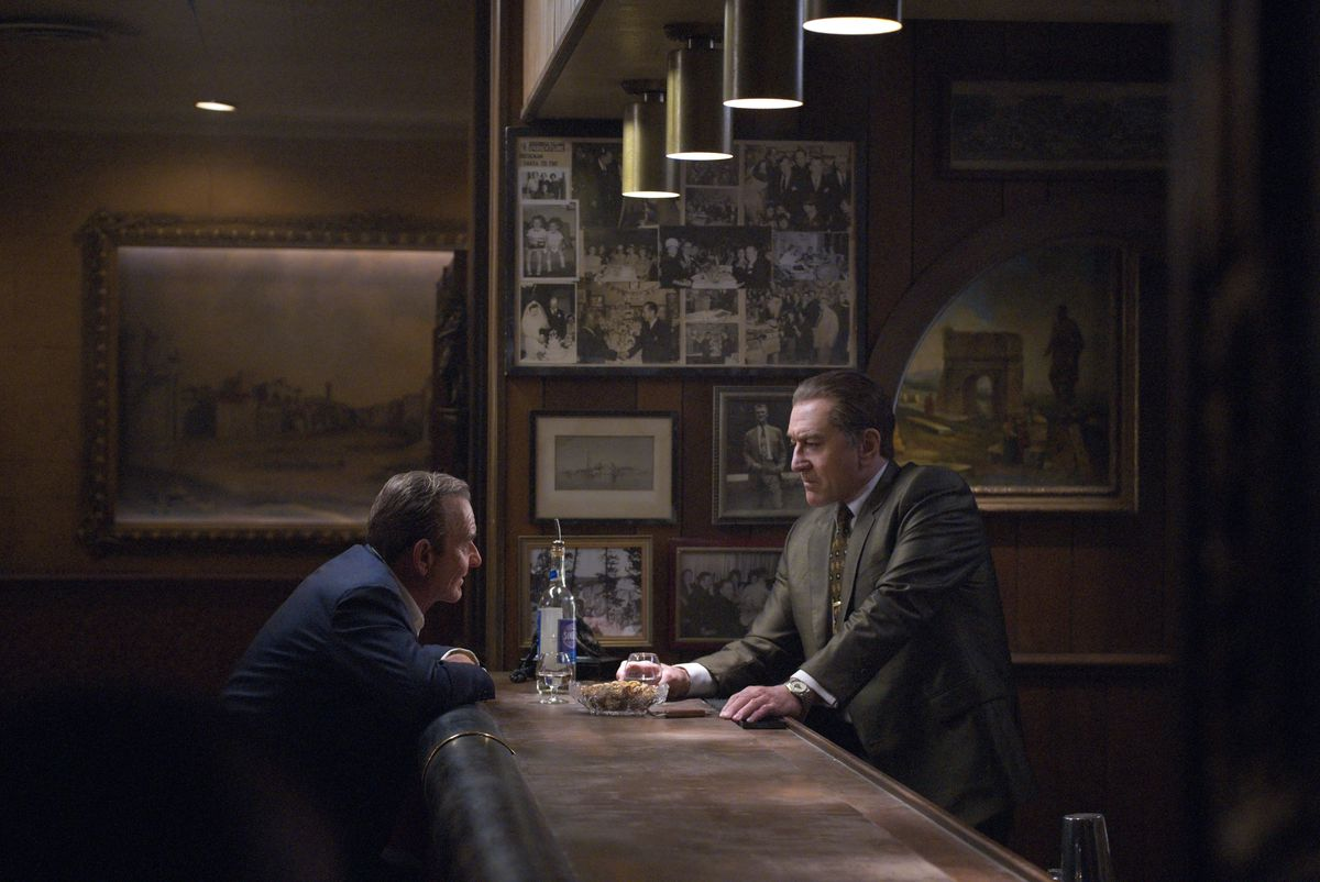 """A scene from the movie """"The Irishman"""" shows Joe Pesci sitting at a bar and Robert De Niro standing behind the bar."""