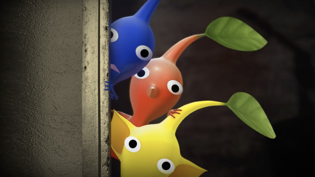 three Pikmin, a blue one, a red one, and a yellow on, peer towards the gaze of the camera