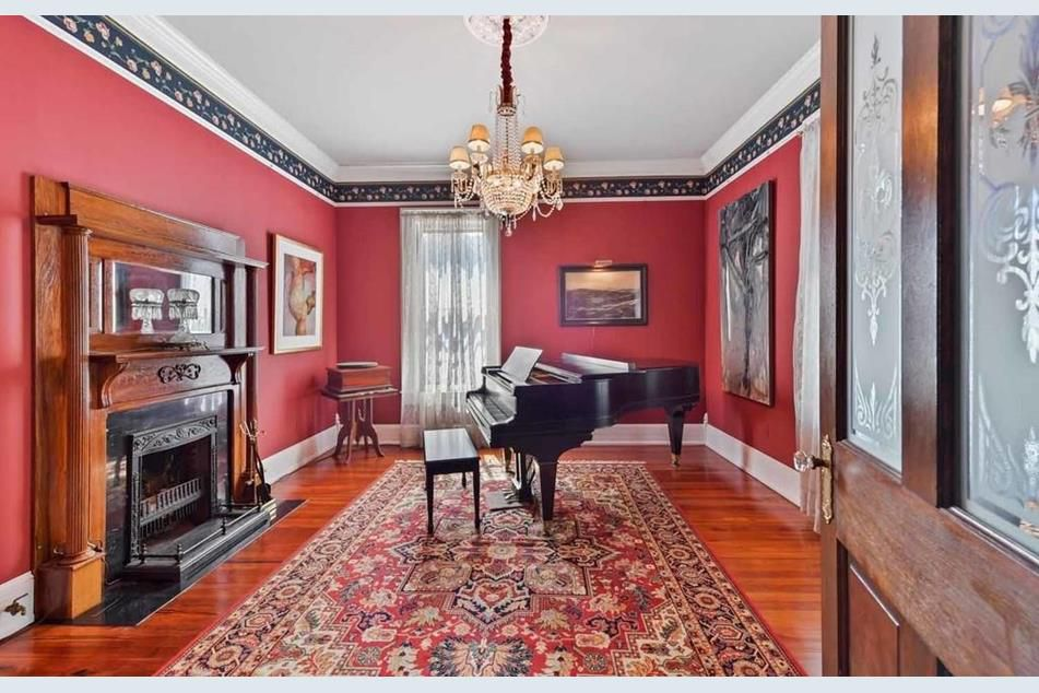 A room with a fireplace, piano, and patterned rug.